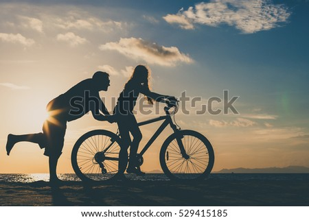 Father and daughter playing on the beach at the sunset time. Concept of happy friendly family.