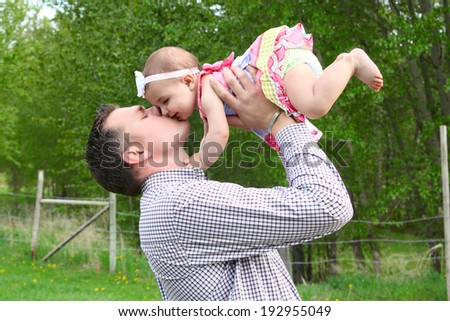 Father and daughter playing outside on the farm - stock photo