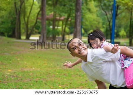Father and daughter playing piggyback at outdoor garden park. Happy Southeast Asian family living lifestyle. - stock photo