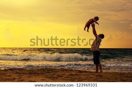 father and daughter playing together on the beach at sunset - stock photo
