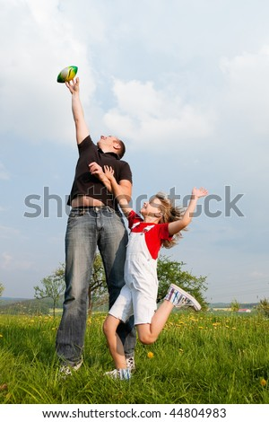 Father and daughter playing with a football, the kid trying to catch it running and jumping - stock photo