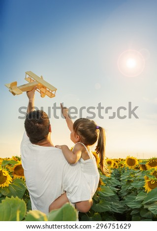 Father and daughter playing with a wooden play toy in a sunflower field - stock photo