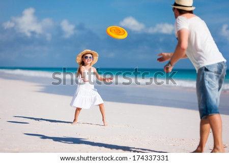 Father and daughter playing with flying disc at beach - stock photo