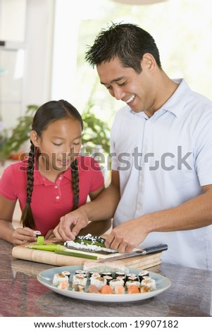 Father And Daughter Preparing Sushi Together - stock photo