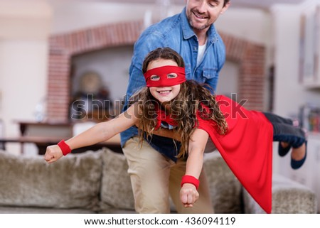 Father and daughter pretending to be superhero in living room at home - stock photo