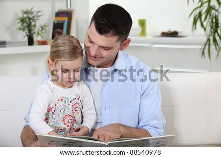Father and daughter reading book - stock photo