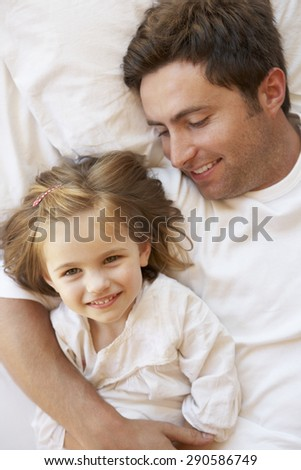 Father And Daughter Relaxing In Bed