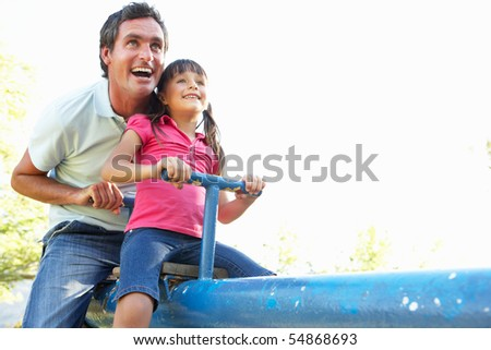 Father And Daughter Riding On See Saw In Playground - stock photo