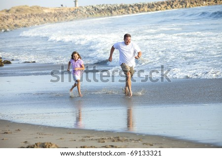 Father and daughter running at the beach - stock photo