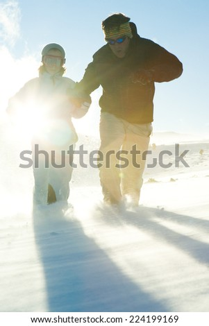 Father and daughter running in snow, dressed in winter clothing, full length - stock photo