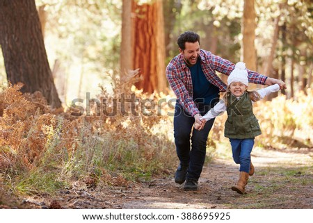 Father And Daughter Running Through Fall Woodland - stock photo