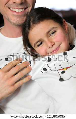 Father and daughter sat on sofa - stock photo