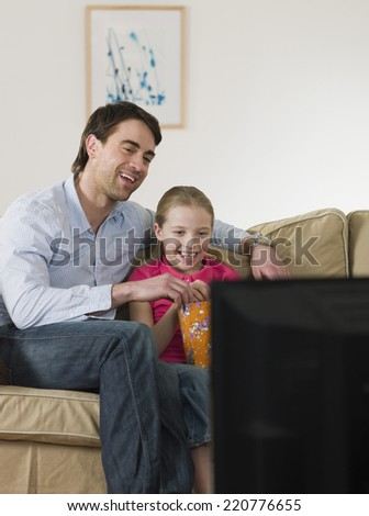 Father and daughter sharing popcorn while watching television - stock photo