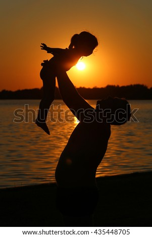 father and daughter silhouette at lake sunset