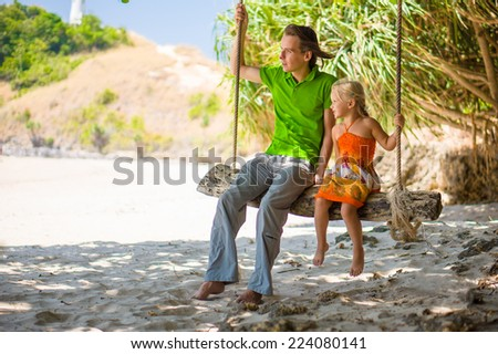 Father and daughter sit on rope swing under palm trees on tropical beach with lighthouse on back - stock photo