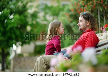 Father and daughter sitting on a bench talking and laughing - stock photo