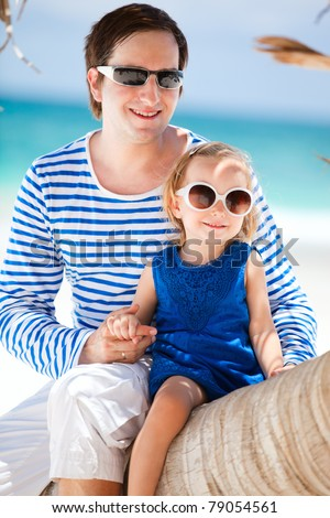 Father and daughter sitting on palm tree enjoying beach vacation