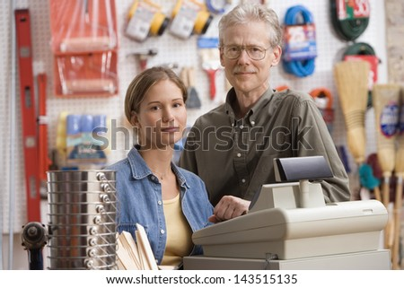 Father and daughter smiling in hardware store - stock photo
