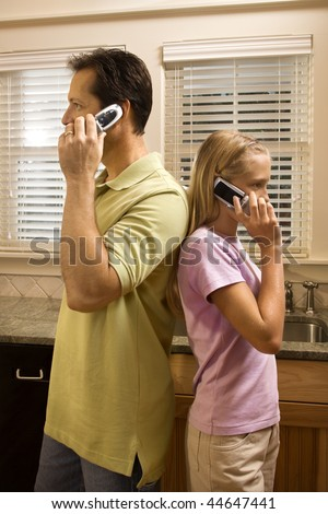 Father and daughter standing back to back talking on cell phones.  Vertically framed shot. - stock photo