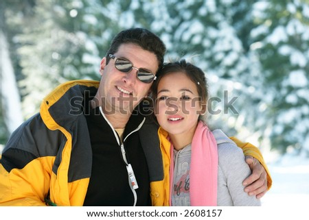 Father and daughter standing in a winter forest - stock photo