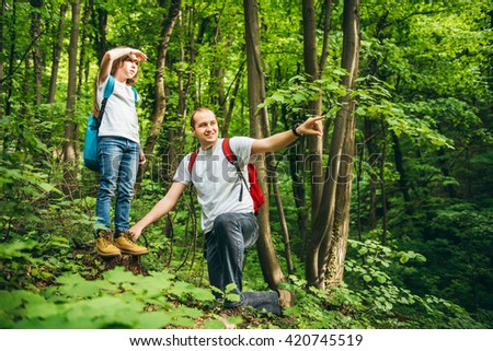 Father and daughter standing on higher ground and looking for a landmarks. - stock photo