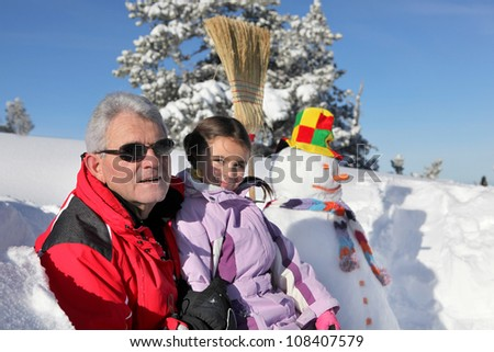 Father and daughter stood by snowman - stock photo