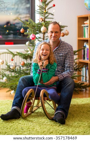 father and daughter together on sled in front of christmas tree - stock photo