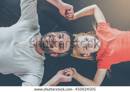 Father and daughter. Top view of happy father and daughter holding hands and smiling at camera while lying on the hardwood floor together - stock photo