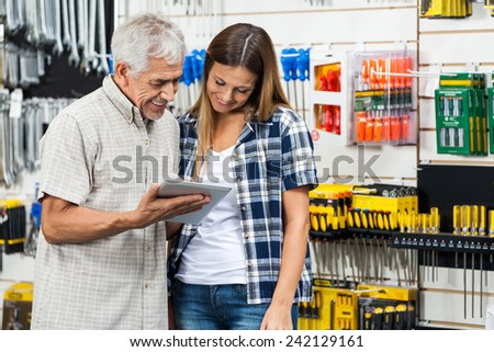 Father and daughter using digital tablet while standing in hardware shop