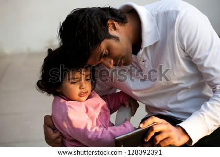 father and daughter using PC tablet, Indian man with his daughter - stock photo