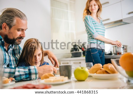 Father and daughter using tablet in the kitchen during breakfast while mother happily watching them. - stock photo