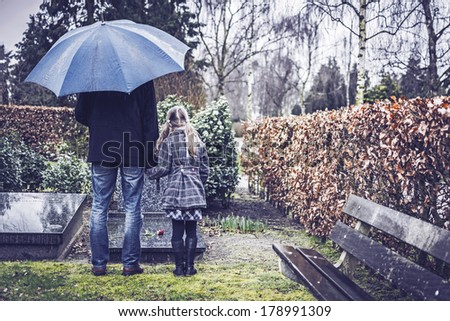 Father and daughter visiting gravestone of deceased mother - stock photo