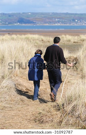 father and daughter walking along coast - stock photo