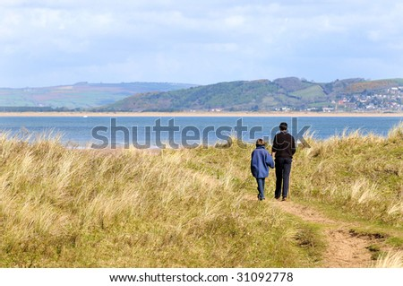 father and daughter walking along the coast - stock photo