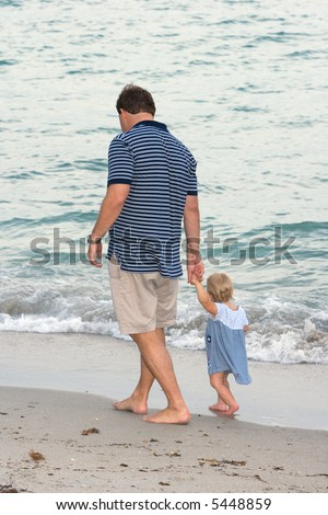Father and Daughter Walking at the Beach Holding Hands
