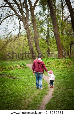 father and daughter walking in the park in the spring afternoon, father's day - concept.vacation, holiday, walk outdoors, family. - stock photo