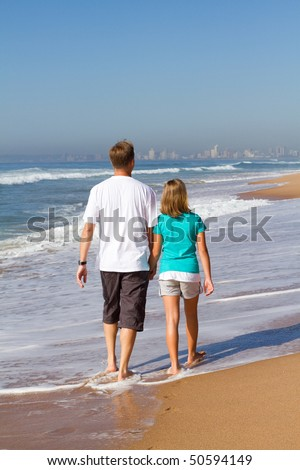 father and daughter walking on beach together