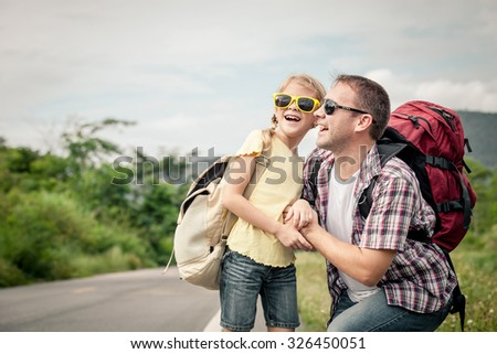 Father and daughter walking on the road at the day time.  Concept of friendly family. - stock photo