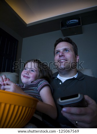 Father and daughter watching movie in home theater - stock photo
