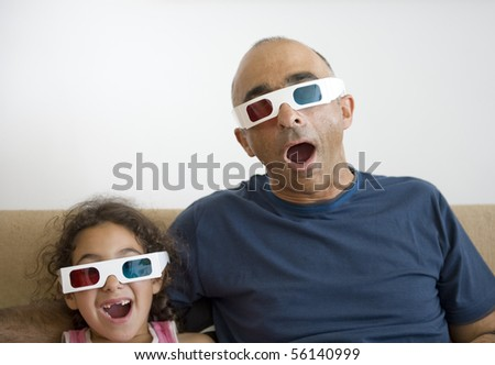 Father and daughter watching television in 3D wearing red and blue glasses - stock photo