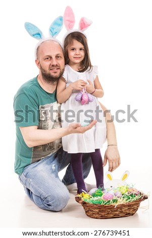 Father and daughter with bunny ears showing Easter eggs from basket - stock photo
