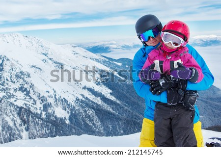 Father and daughter with ski helmets on, in winter mountains - stock photo