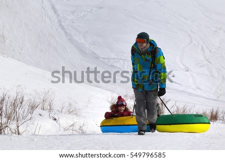 Father and daughter with snow tube at ski resort. Caucasus Mountains, Georgia, region Gudauri.