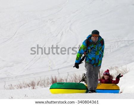 Father and daughter with snow tube at sun day. Caucasus Mountains, Georgia. Ski resort Gudauri. - stock photo