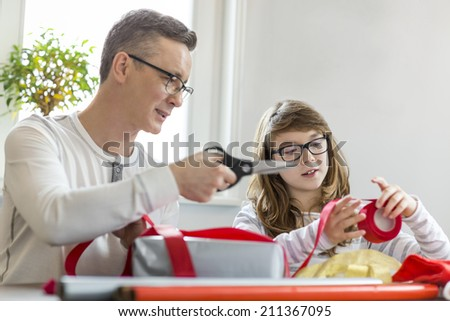 Father and daughter wrapping Christmas presents at home - stock photo