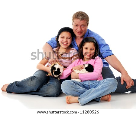 Father and daughters having fun with their 2 pet guinea pigs.