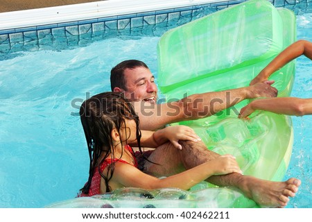 Father and daughters playing in the pool