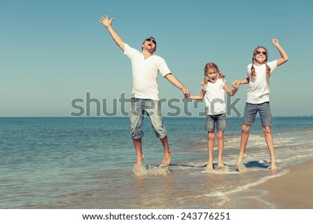 Father and daughters playing on the beach at the day time. Concept of friendly family.