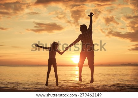 Father and daughters playing on the beach at the sunset time. Concept of friendly family. - stock photo