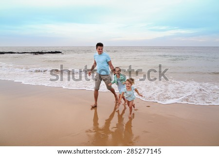 Father and daughters running at the beach - stock photo